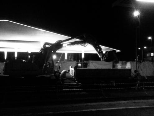 Bauarbeiten an Gleis 1 des Pforzheimer Hauptbahnhofs. Bagger mit Anhänger und Arbeiter. Im Hintergrund der neue Busbahnhof.